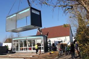 Ein Kran stellt die Pavillon-Elemente auf